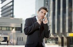 Młody atrakcyjny biznesmen opowiada na telefonie komórkowym outdoors w kostiumu i krawacie Zdjęcie Stock