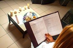 Młody atrakcyjny kobiety obsiadanie w kawiarni z menu Obrazy Stock