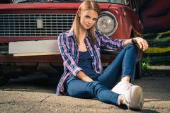 Młody atrakcyjny model siedzi blisko retro samochodu Obrazy Stock