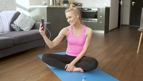 M?ody atrakcyjny sporty kobiety obsiadanie na joga matowym robi selfie z jej telefonem kom?rkowym zbiory