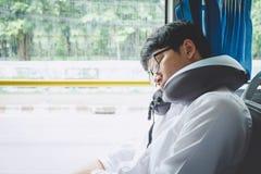M?ody Azjatycki m??czyzna podr??nika obsiadanie na autobusie i dosypianie z poduszki, transportu, turystyki i wycieczki samochodo zdjęcia royalty free