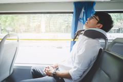 M?ody Azjatycki m??czyzna podr??nika obsiadanie na autobusie i dosypianie z poduszki, transportu, turystyki i wycieczki samochodo zdjęcie stock