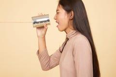 M?ody Azjatycki kobieta krzyk z blaszanej puszki telefonem fotografia stock