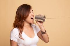 M?ody Azjatycki kobieta krzyk z blaszanej puszki telefonem obraz stock