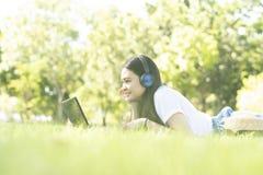 M?ody Azjatycki waman jest pisze puszku na pastylce podczas bierze czas relaks w parku obrazy royalty free