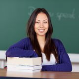 Młody azjatykci kobiety obsiadanie przy szkolnym biurkiem Zdjęcie Stock
