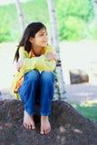 Młody biracial dziewczyny obsiadanie na skale pod drzewami Zdjęcie Stock