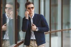Młody biznesmen opowiada na telefonie komórkowym outdoors Zdjęcie Stock