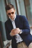 Młody biznesmen opowiada na telefonie komórkowym outdoors Fotografia Royalty Free