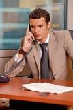 Młody biznesmen opowiada na telefonie w biurze Obrazy Stock