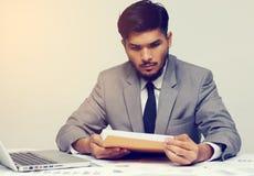 Młody biznesmen otwiera biznesowego raportu dokument Obrazy Royalty Free