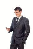 Młody biznesmen patrzeje telefon komórkowego Fotografia Royalty Free
