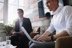 Młody biznesmen pracuje na laptopie przy korporacyjnym spotkaniem Obrazy Royalty Free
