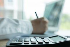 Młody biznesmen pracuje z kalkulatorem, biznesowym dokumentem, i Zdjęcie Royalty Free