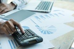 Młody biznesmen pracuje z kalkulatorem, biznesowym dokumentem, i Obrazy Royalty Free