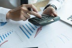 Młody biznesmen pracuje z kalkulatorem, biznesowym dokumentem, i Zdjęcie Stock