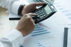 Młody biznesmen pracuje z kalkulatorem, biznesowym dokumentem, i Zdjęcia Stock