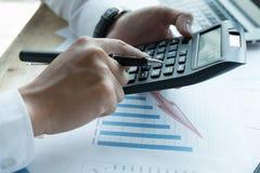 Młody biznesmen pracuje z kalkulatorem, biznesowym dokumentem, i Fotografia Royalty Free