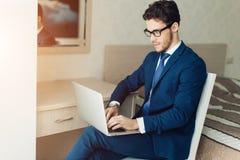 Młody biznesmen pracuje z laptopem przy biurem Obraz Stock