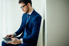 Młody biznesmen pracuje z laptopem przy biurem Fotografia Stock