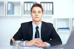 Młody biznesmen przy jego miejscem pracy Zdjęcie Stock