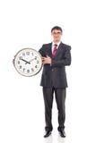 Młody biznesmen trzyma zegar Obrazy Royalty Free