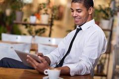 Młody biznesmen w kawowej przerwie pracuje na jego ipad Obraz Stock