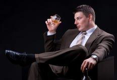 Młody biznesmen z alkoholicznym napojem Fotografia Stock