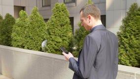 M?ody biznesmena odprowadzenia puszek ulica i pisze wiadomo?ci na smartphone zdjęcie wideo