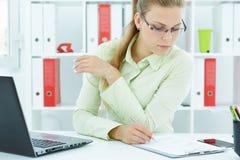 Młody bizneswoman robi notatkom w papierach w biurze Obraz Royalty Free