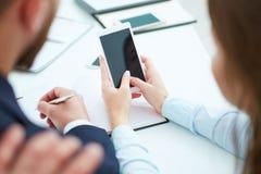 Młody bizneswomanu seansu telefonu ekran koledzy w biurze Zdjęcie Stock