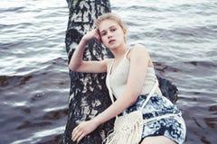 M?ody blond kobiety obwieszenie na brzozy drzewie przy jeziornym brzeg, wakacje plenerowy styl ?ycia zdjęcia royalty free