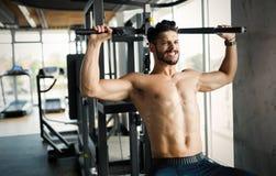 Młody bodybuilder szkolenie w gym na maszynie Zdjęcie Stock