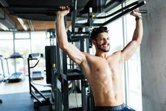 Młody bodybuilder szkolenie w gym na maszynie Zdjęcia Stock
