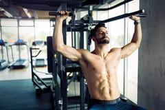 Młody bodybuilder szkolenie w gym na maszynie Obrazy Royalty Free