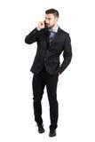 Młody brodaty biznesmen opowiada na telefonu odprowadzeniu w kierunku kamery patrzeje daleko od w kostiumu Zdjęcie Stock
