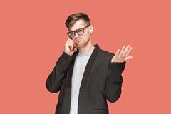 Młody caucasian biznesmen opowiada na telefonie komórkowym na czerwonym tle Zdjęcie Royalty Free