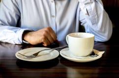 M?ody cz?owiek po przyjemnego herbacianego przyj?cia odpoczywa i opowiada na telefonie w kawiarni biznesowy lunch, biznesowi spot obrazy royalty free