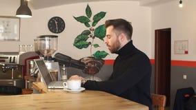 M?ody cz?owiek pracuje na jego laptopie w sklepie z kaw? w ranku zdjęcie wideo