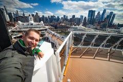 M?ody cz?owiek robi selfie z ogromnym statkiem wycieczkowym i Nowy Jork miastu na tle Poj?cie szcz??liwy wakacje i podr??owa? fotografia royalty free