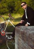 Młody elegancki facet z bicyklem outdoors Obrazy Royalty Free