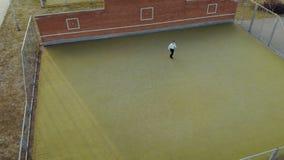 M?ody energiczny facet, uliczny tancerz w czerni spodniach i bia?y pulower, wykonuje pi?knych ruchy na zdjęcie wideo