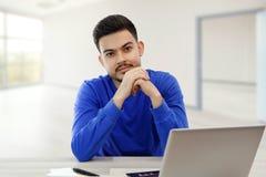 M?ody faceta obsiadanie przy laptopem w poszukiwaniu pracy, robi biznesowi na internecie na lekkim tle obraz royalty free
