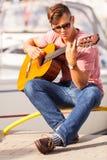 Młody gitarzysty obsiadanie na molu Obraz Stock