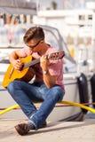 Młody gitarzysty obsiadanie na molu Obrazy Royalty Free