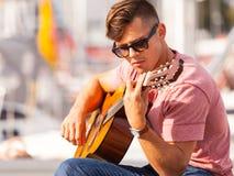 Młody gitarzysty obsiadanie na molu Fotografia Royalty Free