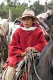 Młody kowboj na konia tylnym jest ubranym czerwonym poncho Zdjęcia Royalty Free