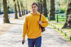 M?ody miastowy m??czyzna u?ywa smartphone odprowadzenie w ulicie w miastowym parku w Londyn obrazy royalty free