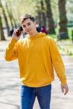 M?ody miastowy m??czyzna u?ywa smartphone odprowadzenie w ulicie w miastowym parku w Londyn fotografia royalty free