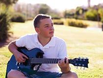 Młody muzyk siedzi na trawie Zdjęcie Royalty Free